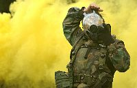 A U.S. Navy Photographer's Mate practices donning her gas mask during an exercise