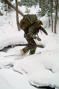 A student at the Navy Survival, Evasion, Resistance and Escape (SERE) school crosses a frozen creek.